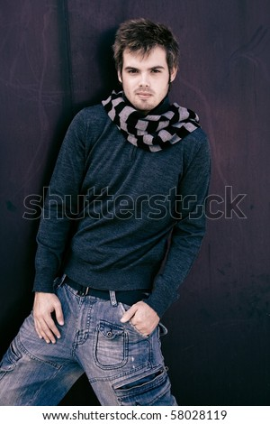 attractive guy sheltered from the cold and posing for the camera - stock photo