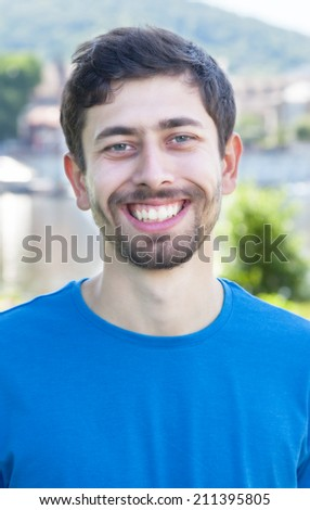 Attractive guy with beard and blue shirt is happy - stock photo
