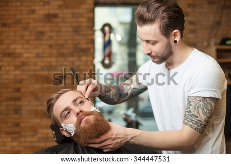 Attractive hairdresser is shaving male beard with the knife. He is standing and looking at human face with joy. The bearded man is sitting with seriousness - stock photo