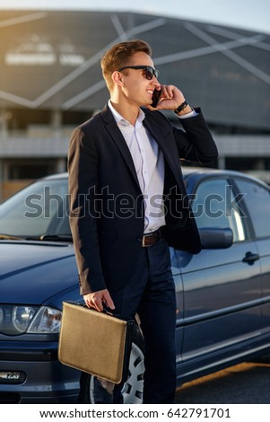 Attractive handsome businessman with diplomat talking on smart phone near the car