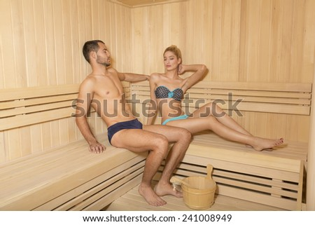 Attractive handsome couple relaxing in sauna - stock photo