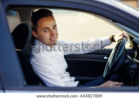 Attractive handsome smiling man in white shirt driving an expensive car
