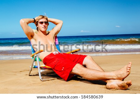 Attractive Handsome Young Man Enjoying Sunny Day on the Beach - stock photo