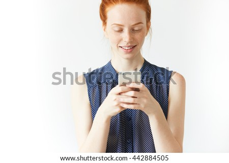 Attractive happy and cheerful young freckled redhead woman wearing sleeveless shirt chatting with her boyfriend on Internet-enabled mobile phone, looking joyful and interested in chat, smiling - stock photo