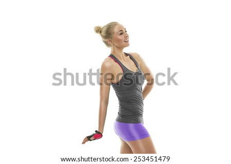 Attractive happy athletic young blond woman with a fit toned body posing sideways with her hand on her hip showing off her sexy muscular physique, isolated on white