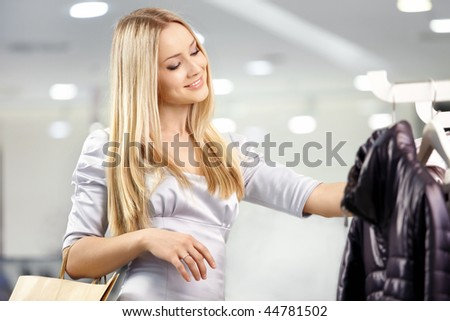 Attractive happy blonde chooses clothes in shop - stock photo