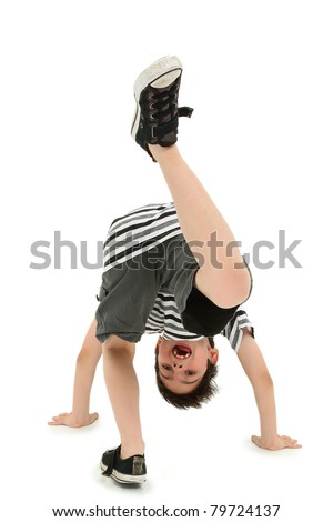 Attractive happy boy doing cartwheel on white floor. - stock photo