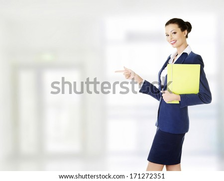 Attractive happy businesswoman pointing on copy space