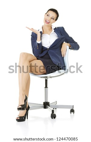 Attractive happy businesswoman sitting on office chair and showing copy space. Isolated on white. - stock photo