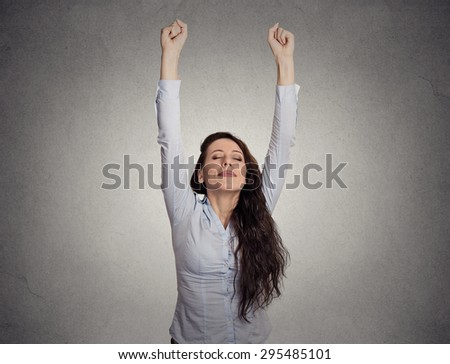 attractive happy businesswoman with her arms raised on gray wall background  - stock photo