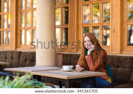 Attractive happy cheerful young woman with beautiful long red hair in leather jacket sitting with cellphone and drinking tea in outdoor cafe in autumn - stock photo