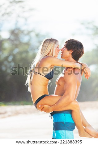 Attractive Happy Couple Kissing on Beautiful Sunny Beach  - stock photo
