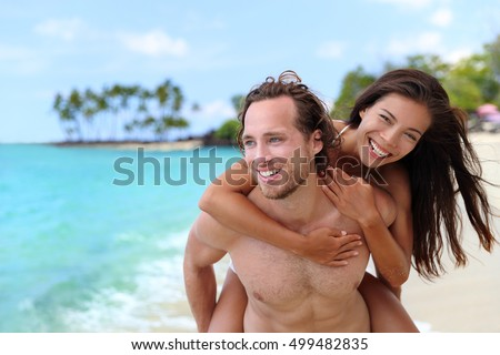 Attractive happy couple laughing having fun piggybacking on tropical beach. Caucasian man carrying Asian girlfriend having fun laughing on travel vacation. Healthy happy interracial people.