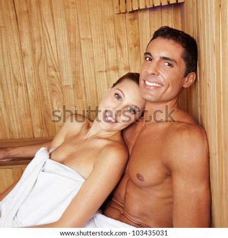 Attractive happy couple relaxing together in a sauna - stock photo