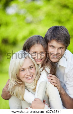 Attractive happy family with a child outdoors - stock photo