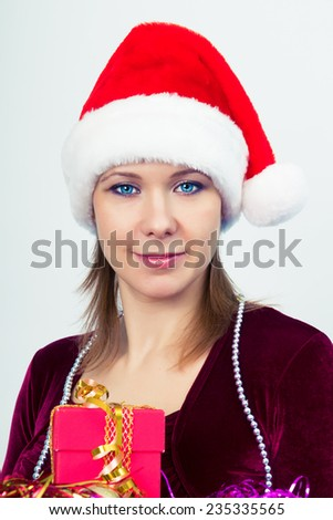 Attractive happy girl in santa hat with gift boxes - stock photo
