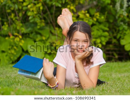 Attractive happy girl with book lying down on grass - stock photo