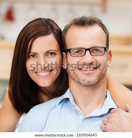 Attractive happy married couple posing with their heads close together looking directly into the camera - stock photo