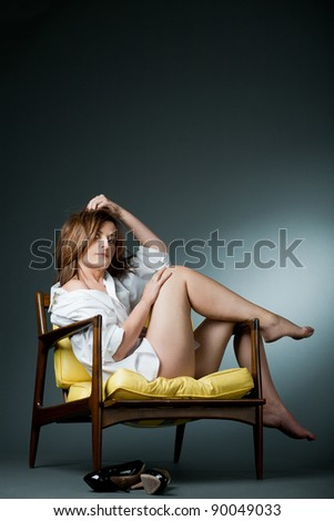 Attractive happy mature woman relaxing on chair. - stock photo