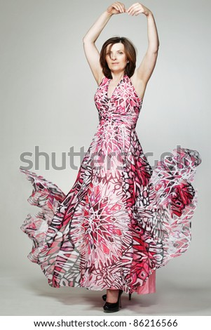 Attractive happy middle-aged woman in red dress. - stock photo
