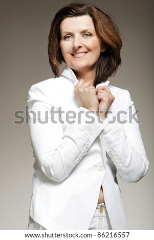 Attractive happy middle-aged woman in white suit. - stock photo