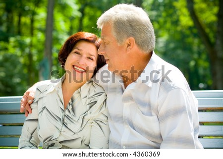 Attractive happy smiling senior couple embracing outdoors. Focus on man. - stock photo