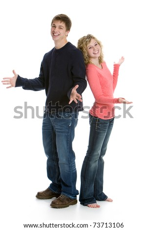 Attractive happy teenage couple standing back to back in studio with white background - stock photo