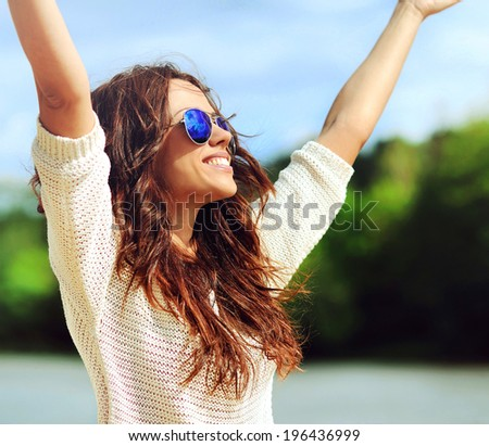 Attractive happy woman in sunglasses enjoying freedom outdoors with hand raised - stock photo