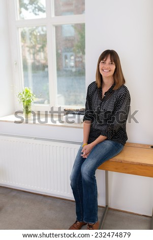 Attractive happy woman sitting on a wooden childs school desk alongside a bright airy window at home smiling at the camera - stock photo