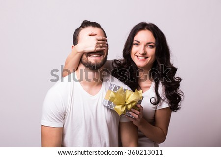 Attractive happy woman with big toothy smile holding boyfriends eyes giving him a present for Valentine's day. Girl look at camera. Caucasian couple.Grey background. - stock photo