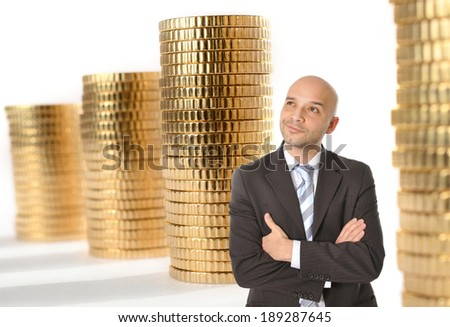 Attractive Happy Young Business Man with bald head Thinking and Dreaming of Big Money in the form of huge stacks of gold coins aligned in the Background - stock photo