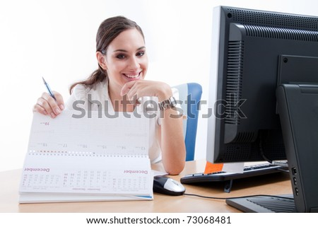 Attractive happy young businesswoman behind her desk. Checking her schedule.