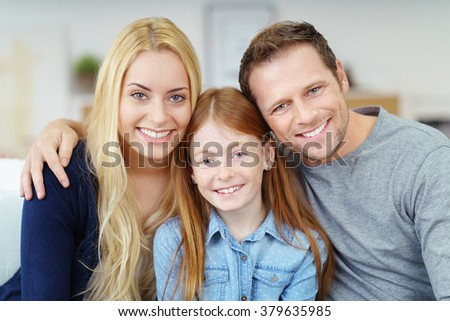 Attractive happy young family posing at home sitting close together on the sofa with a young pretty girl flanked by her parents all smiling at the camera - stock photo