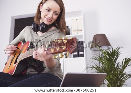 Attractive happy young girl with long brown hair playing music on guitar while using tablet