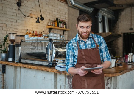 Attractive happy young waiter with beard in brown apron using tablet in cafe - stock photo