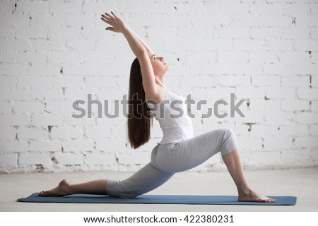 Attractive happy young woman working out indoors. Beautiful model doing exercises on blue mat. Standing in low lunge exercise (horse rider or ashwa sanchalasana pose). Full length. Side view - stock photo