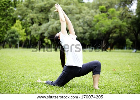 Attractive Healthy Asian Woman doing yoga in the park - stock photo