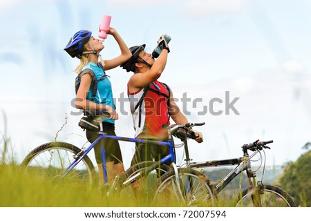 Attractive, healthy couple drink from their water bottles on mountain bikes. active outdoor lifestyle concept - stock photo