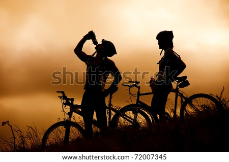 Attractive, healthy couple drink from their water bottles on mountain bikes, silhouette at sunset. active outdoor lifestyle concept - stock photo