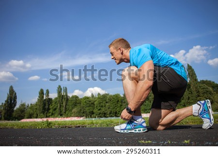 Attractive healthy man ties the laces in stadium. He takes a seat and bents his knee in profile. The sportsman is looking forward with desire. There is copy space in left side - stock photo