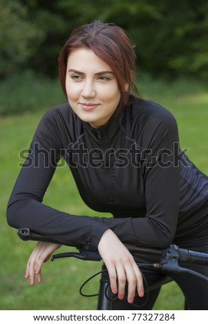 Attractive, healthy young woman with mountain bike is having a break - stock photo