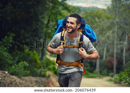 Attractive hiker with big traveling rucksack moving up on the mountain trail and smiling, happy traveler overcome big way smiling looking away, adventure travel and discovery - stock photo