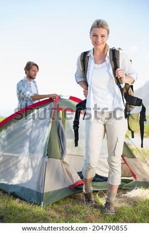 Attractive hiking blonde smiling at camera while partner pitches tent on a sunny day - stock photo