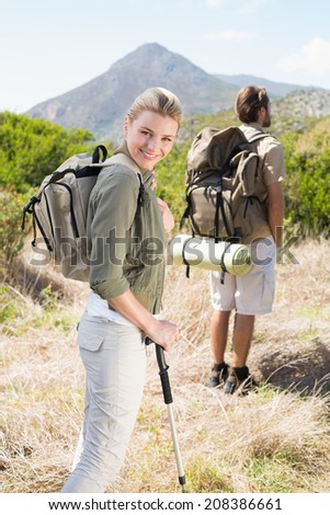 Attractive hiking couple walking on mountain trail woman smiling at camera on a sunny day