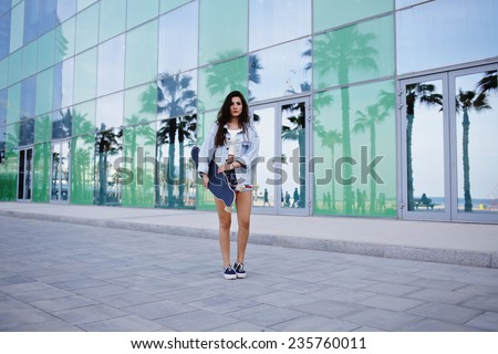 Attractive hipster girl holding her longboard standing on the road with beautiful background with reflected palm trees, charming young woman looking to the camera holding skateboard - stock photo