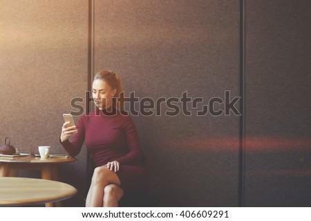 Attractive hipster girl is reading fashion website via cell telephone application while is sitting in cafe, young woman using her smart phone while is sitting in contemporary coffee shop. Copy space  - stock photo