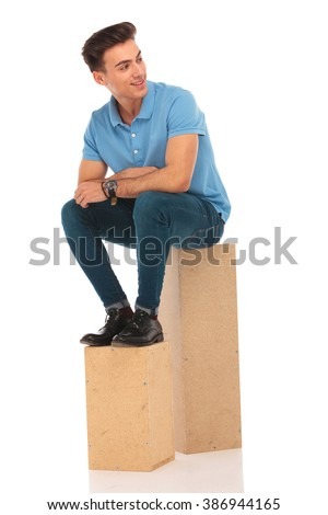 attractive hipster seated on boxes in isolated studio background while looking away from the camera - stock photo