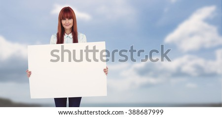 Attractive hipster woman holding white card against beach with blue sky - stock photo