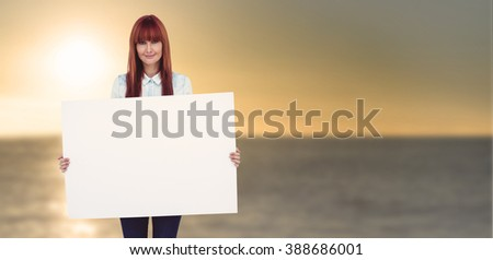 Attractive hipster woman holding white card against sunset of a beautiful day - stock photo