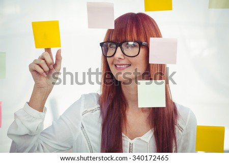 Attractive hipster woman pointing sticky notes in her office - stock photo